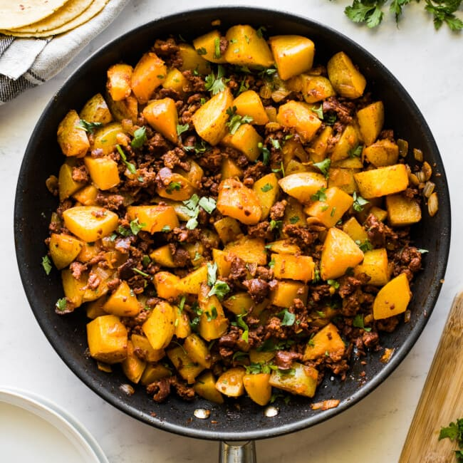Papas con chorizo (or potatoes with chorizo) in a large skillet.