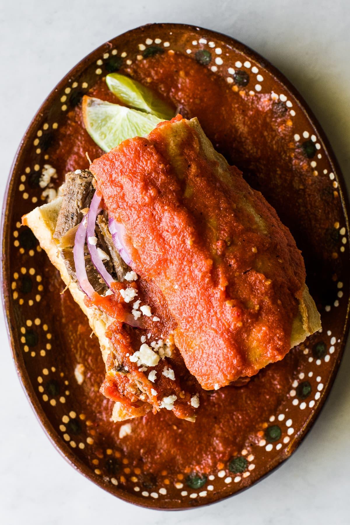 A torta ahogada Mexican sandwich on a traditional clay plate.