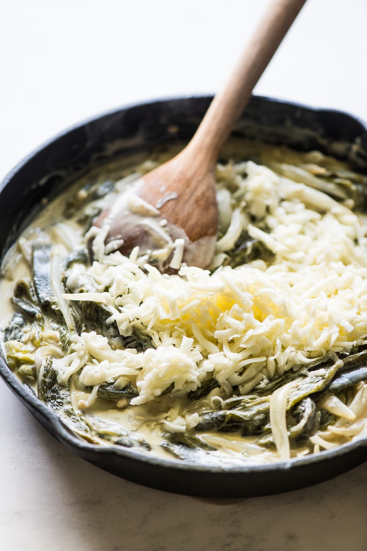 Shredded Oaxaca cheese being stirred into rajas con crema skillet.