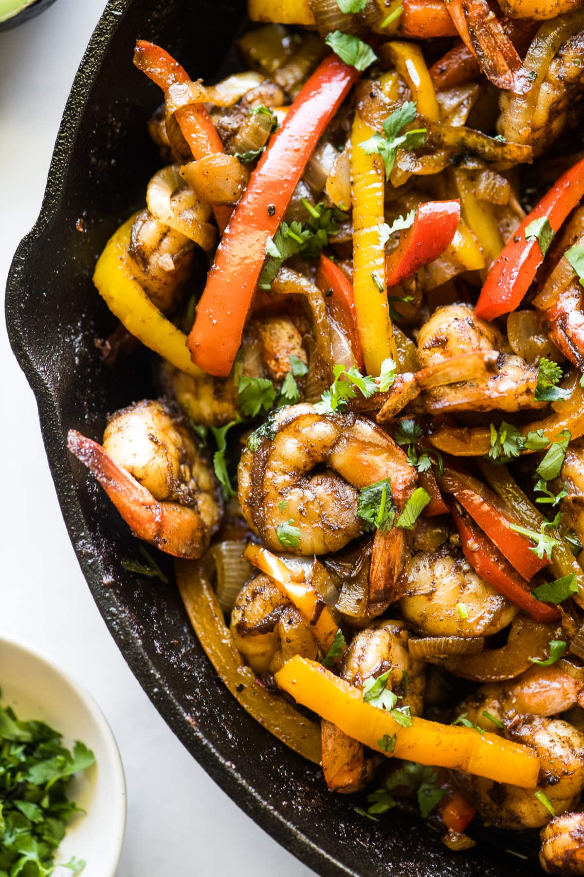 Shrimp fajitas with bell peppers in a skillet.