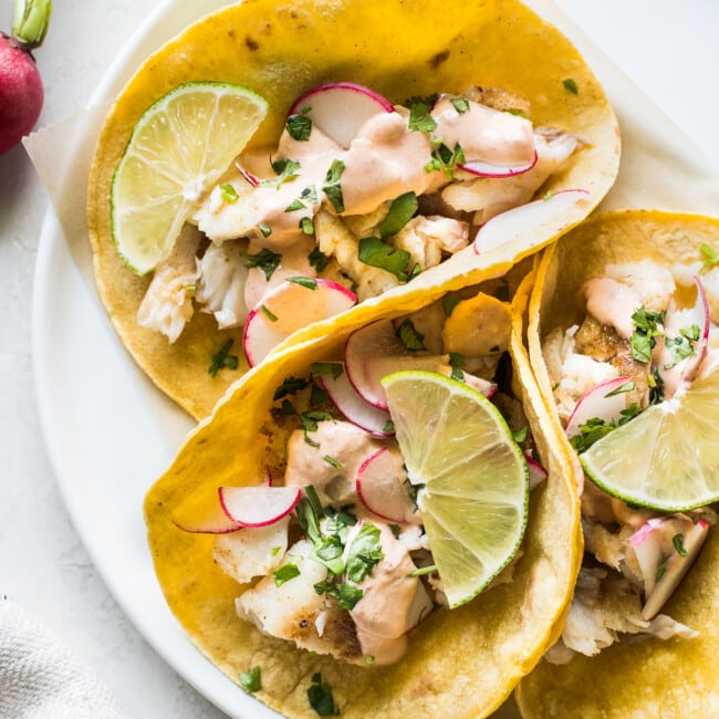 Tilapia fish tacos topped with cilantro and chipotle lime crema.