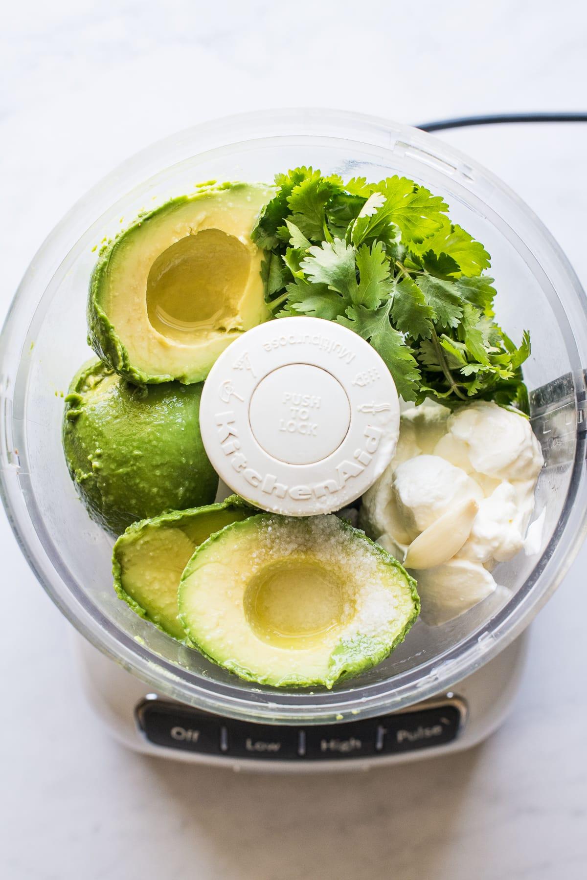Avocado crema ingredients in a food processor.