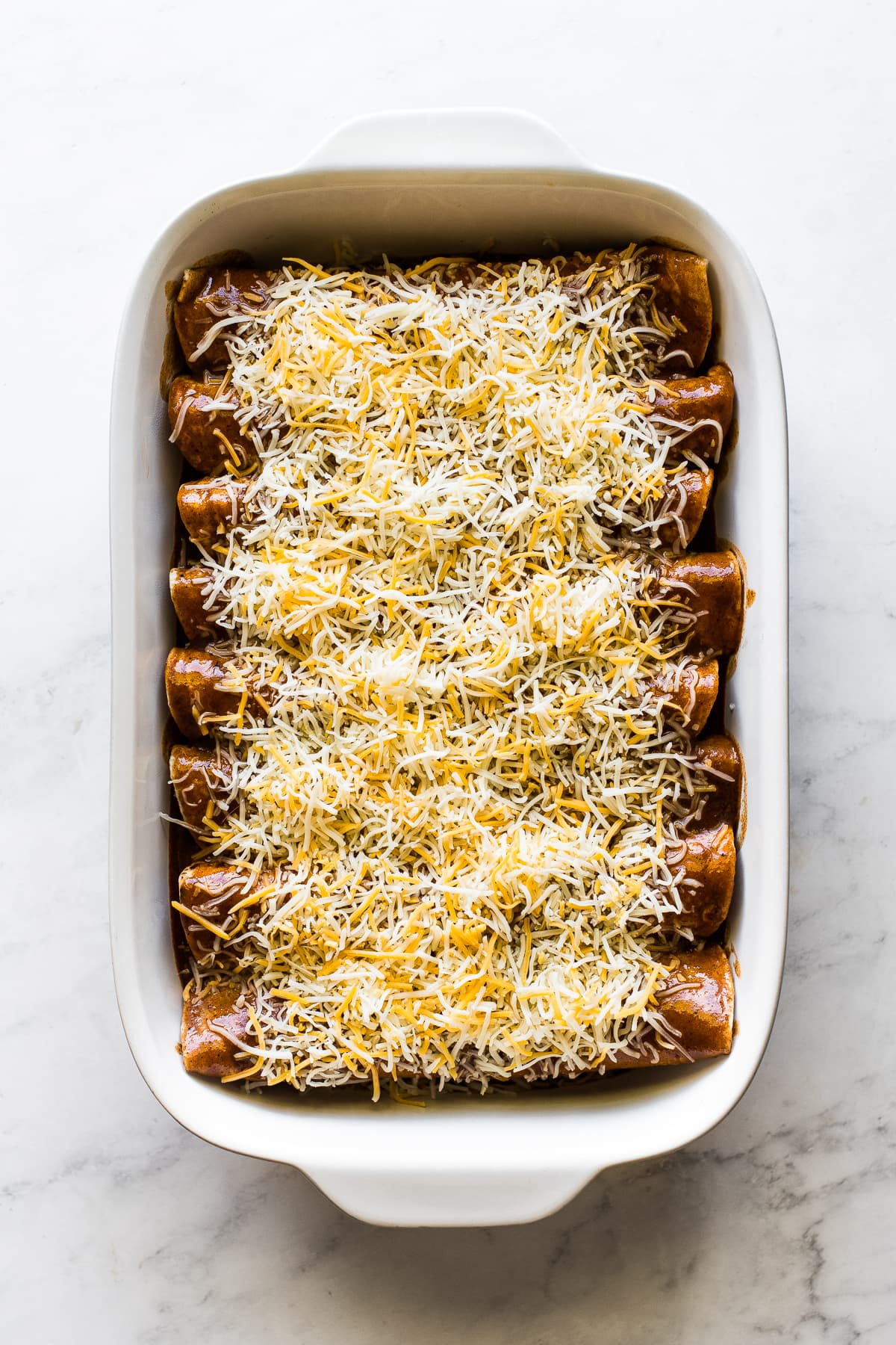 Enchiladas ready to be baked in a pan topped with enchilada sauce and shredded cheese.