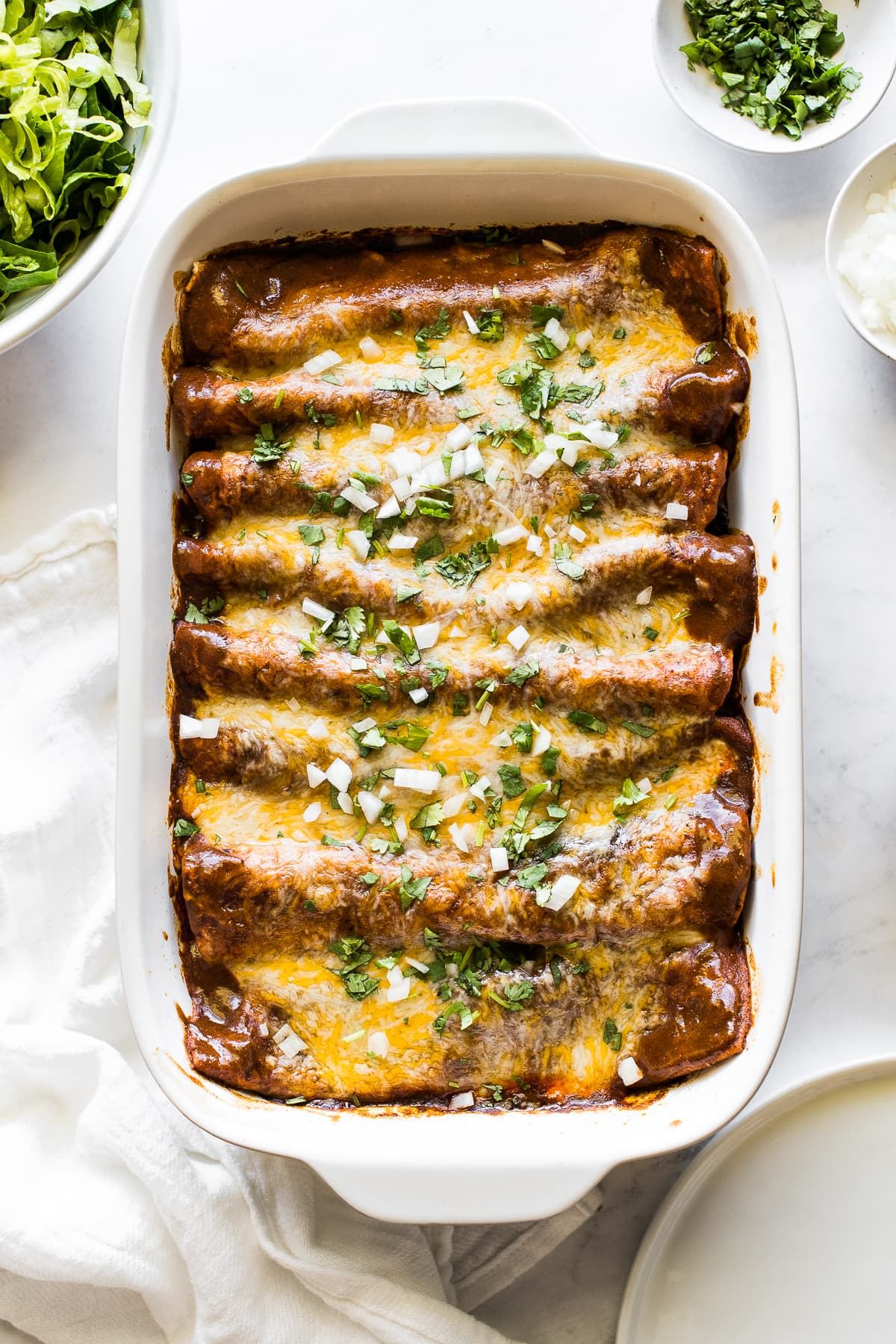 Baked beef enchiladas in a baking dish topped with cilantro and onions.