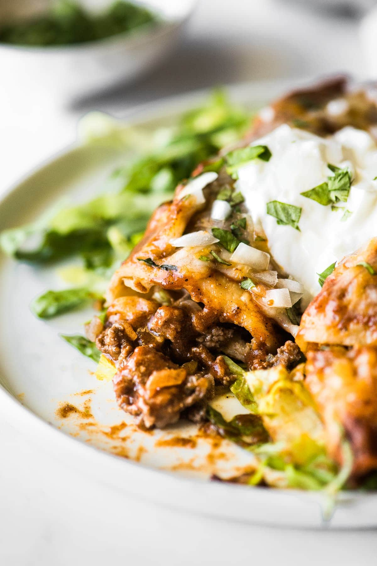 Beef enchiladas topped with sour cream on a bed of shredded lettuce.