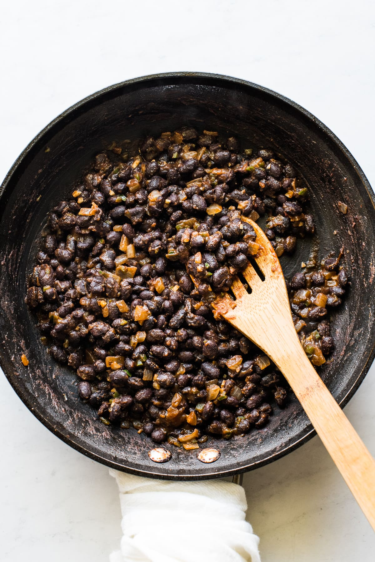 Black beans cooking in a skillet with spices and seasonings.