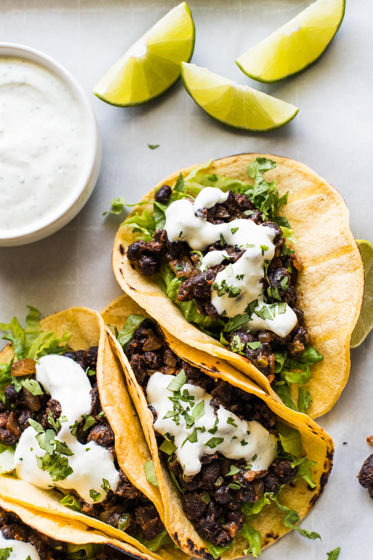 Black bean tacos in a corn tortilla with lime wedges.