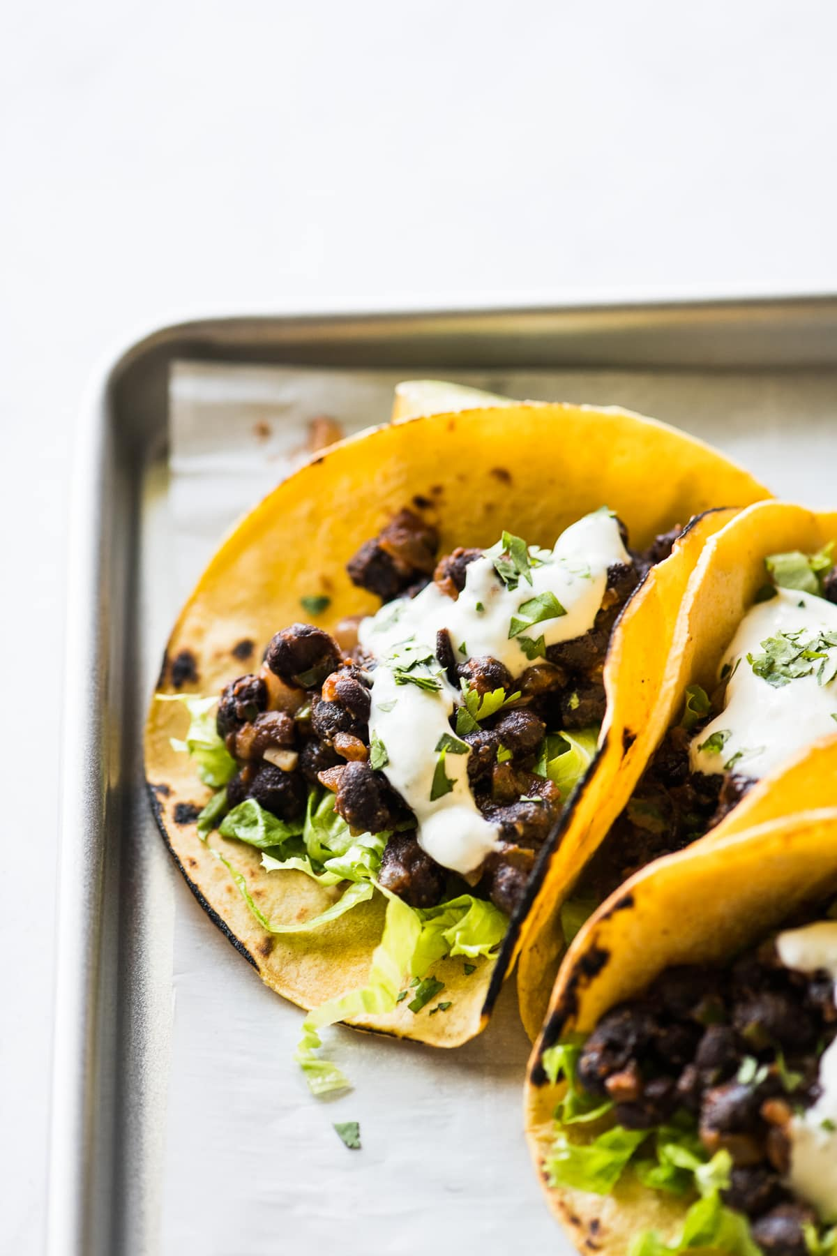 Black bean tacos topped with sour cream.