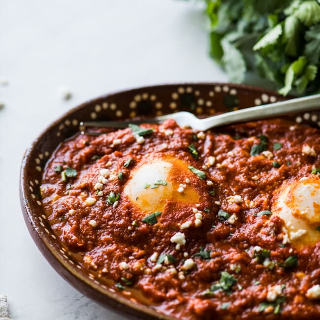 Huevos ahogados in a red salsa.