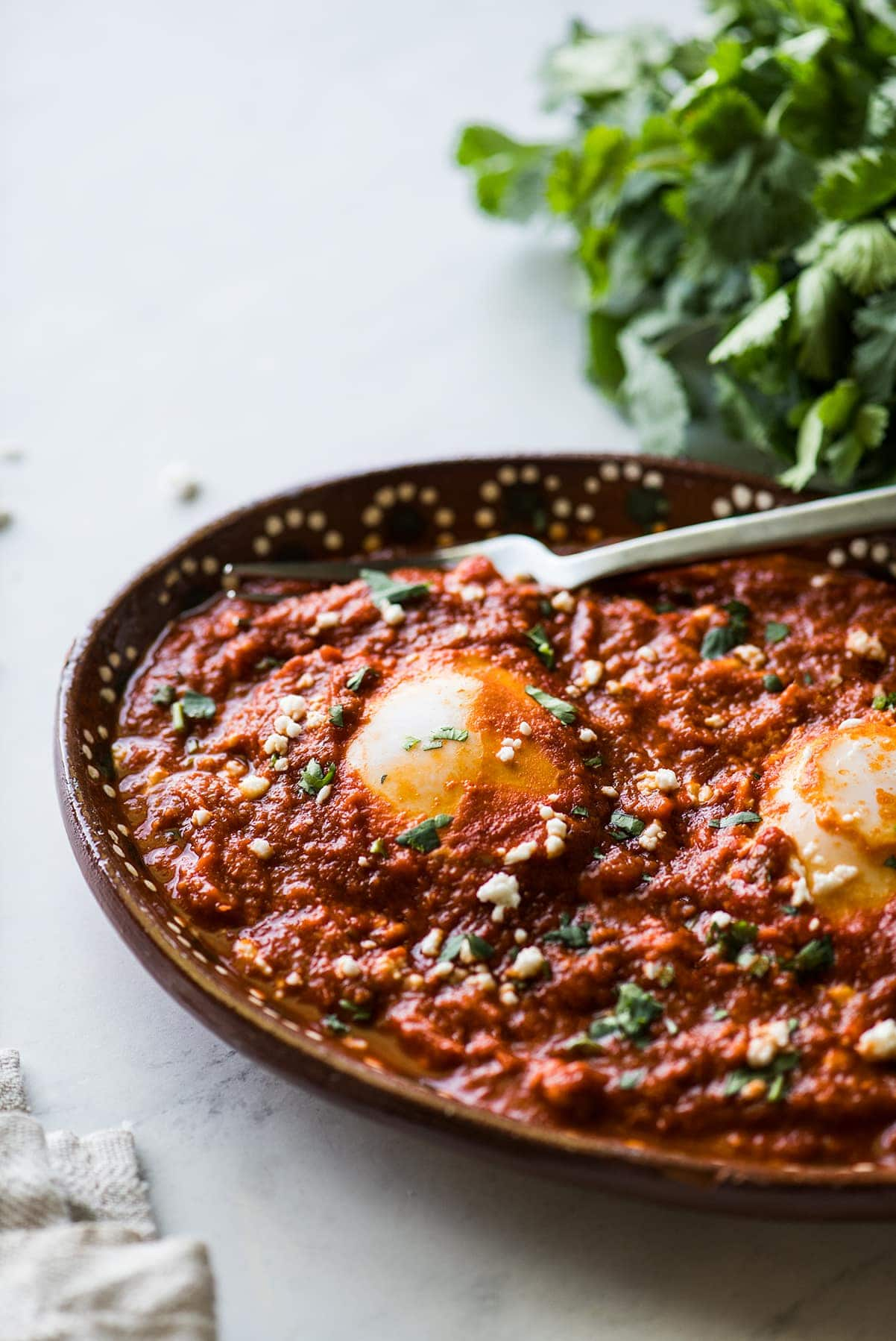 Huevos ahogados in a red salsa.