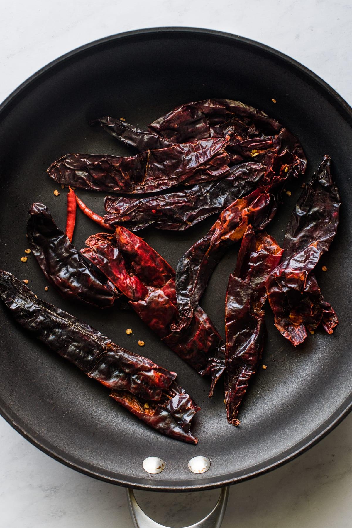 Guajillo chiles toasting on a skillet.