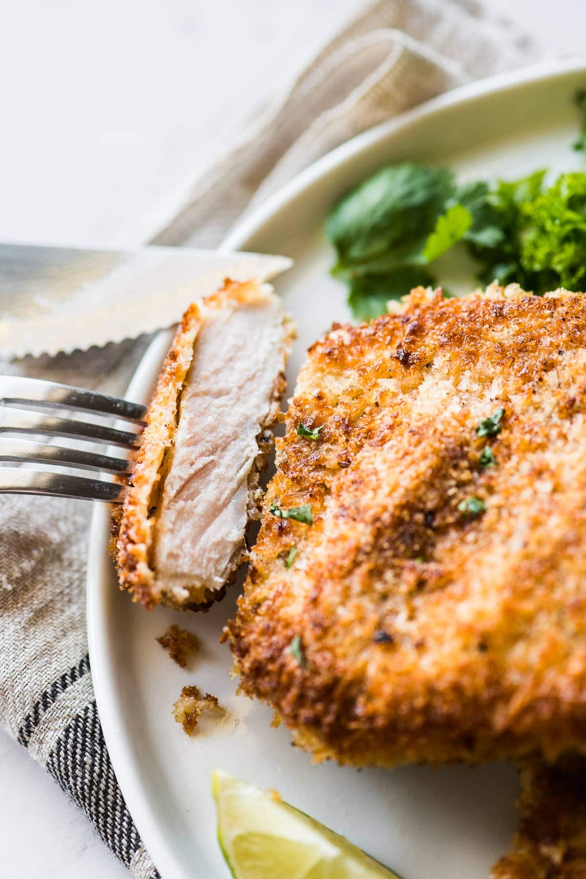 A slice of crispy breaded pork cutlet on a fork ready to eat.