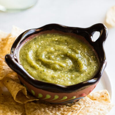 Salsa verde in a Mexican bowl next to some tortilla chips.