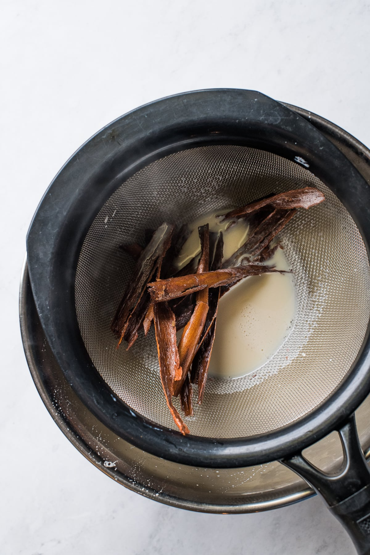 Cinnamon stick pieces in a strainer for making atole.