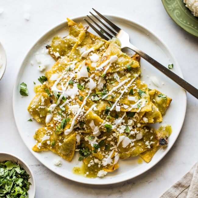 Chilaquiles verdes on a white plate.