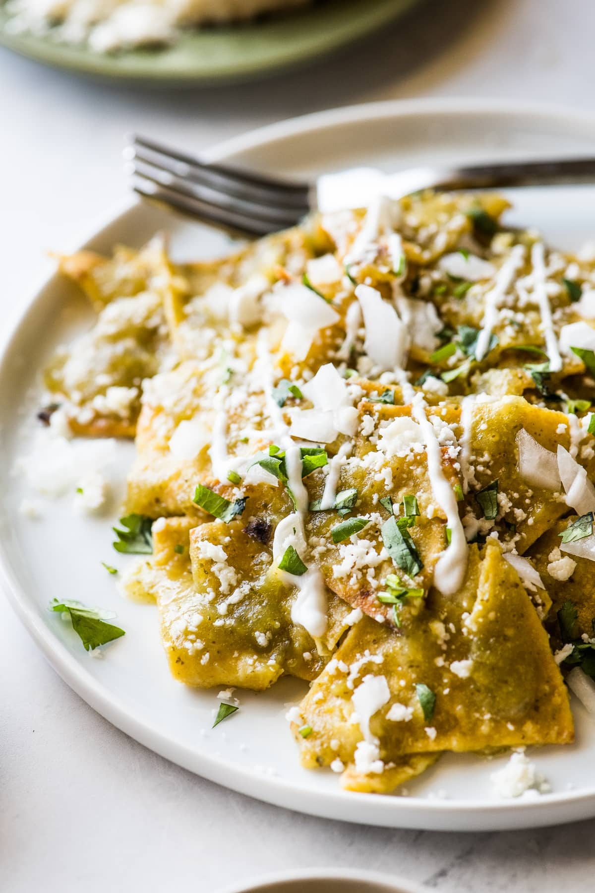 Chilaquiles verdes topped with crema, cilantro, and onions.