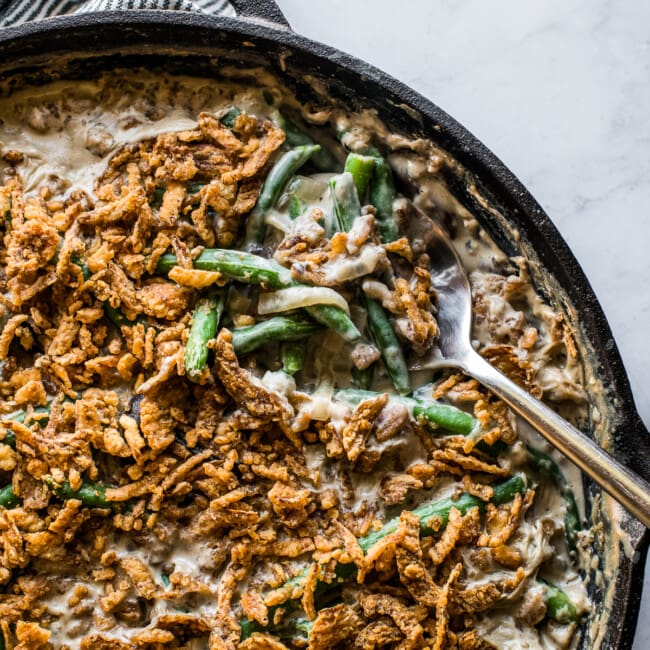 A spoon grabbing a portion of green bean casserole to serve.