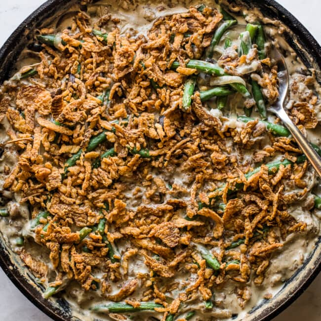 Green bean casserole recipe in a large skillet ready to serve.
