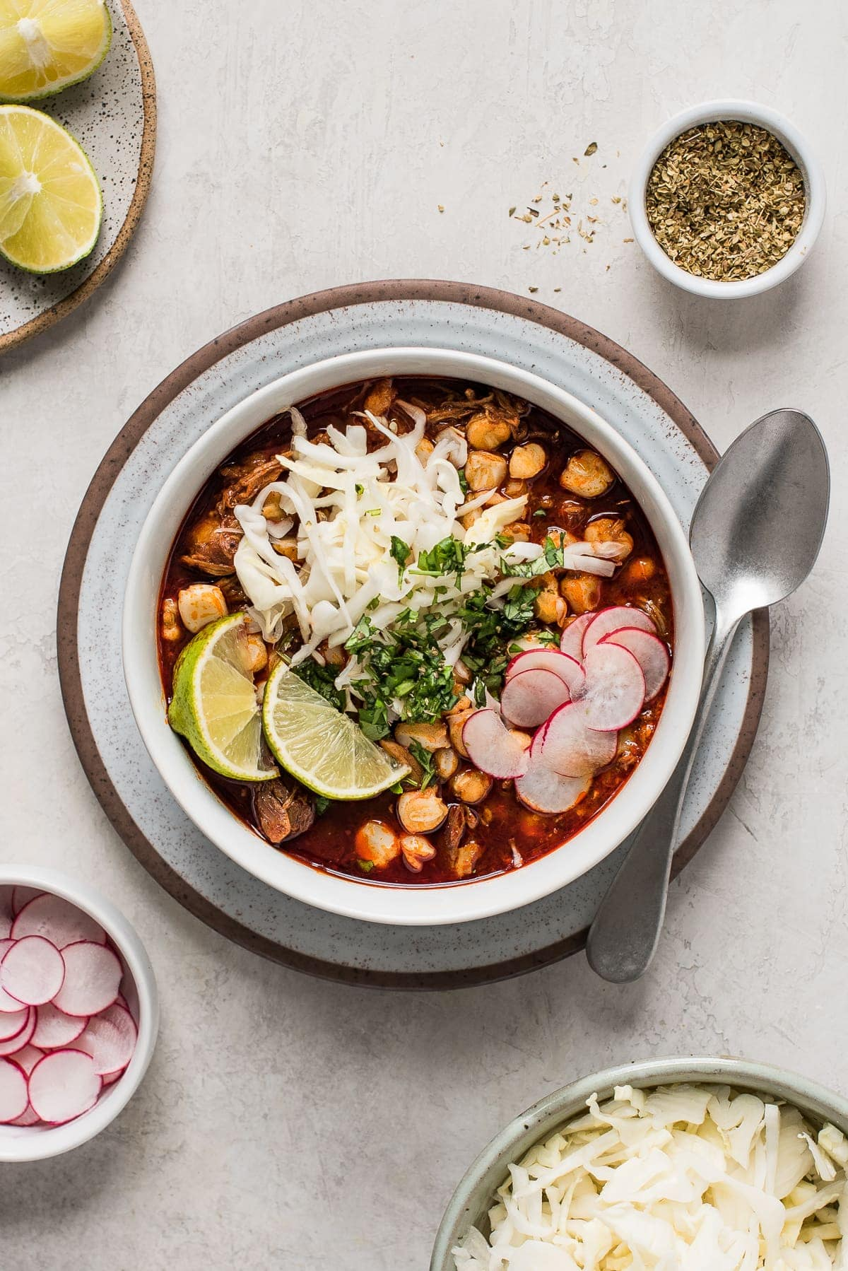 Red posole in a bowl topped with cabbage, radishes, cilantro, and limes.