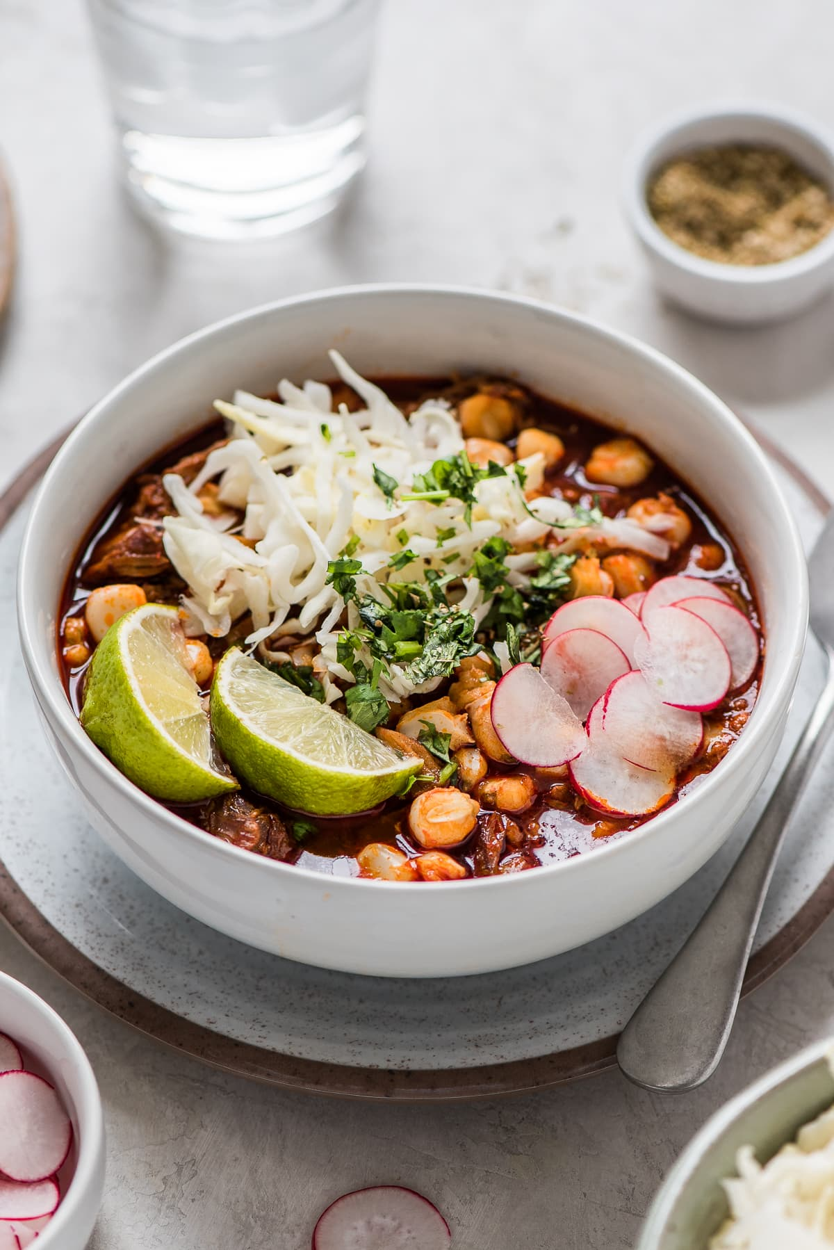Red posole in a bowl topped with sliced radishes, cilantro, and more toppings.