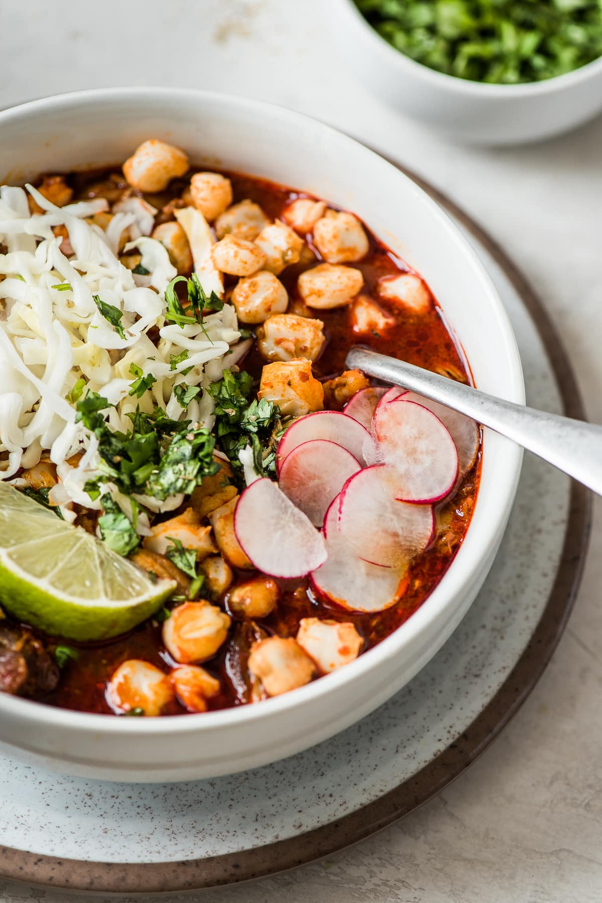 Red posole in a bowl with hominy and toppings.