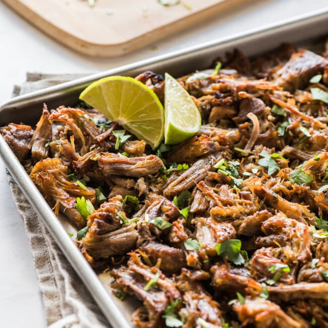 Crispy pressure cooker carnitas topped with cilantro on a baking sheet.