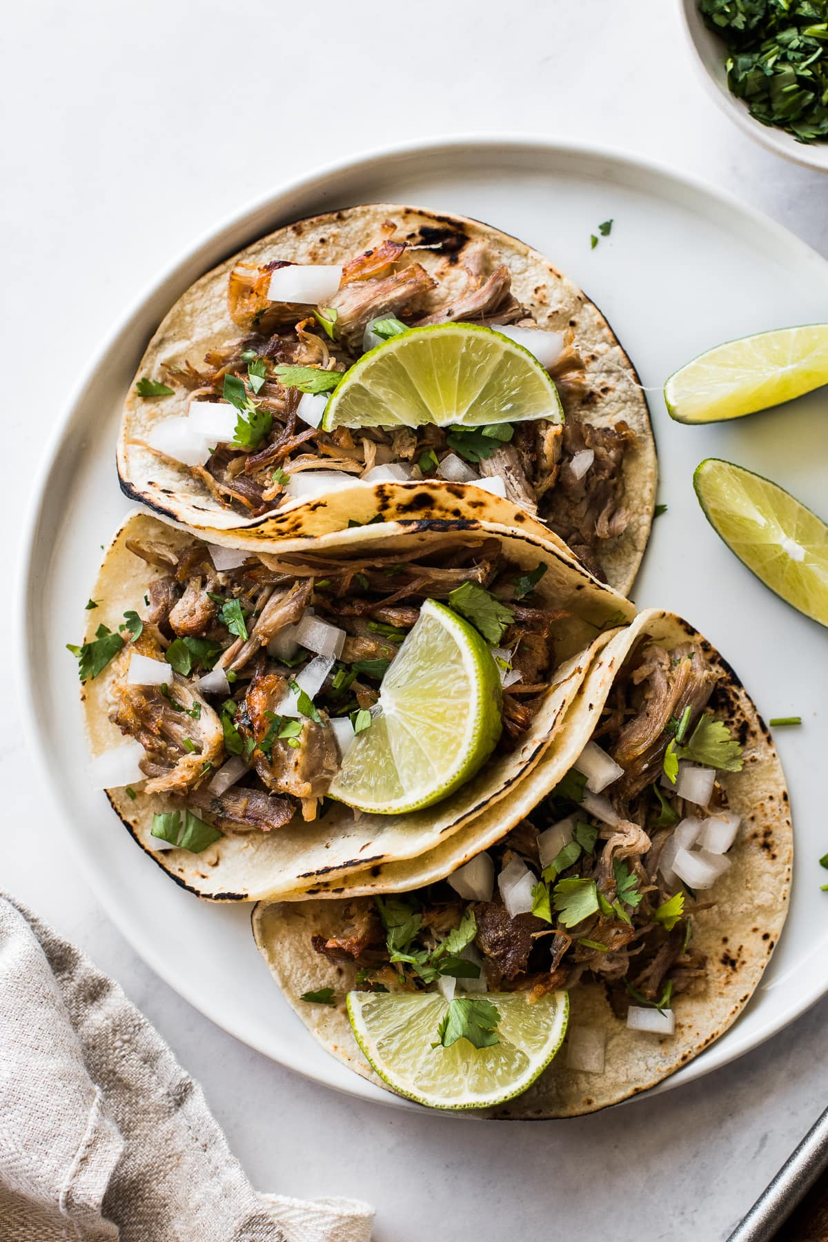 Instant Pot carnitas in tacos topped with onions, cilantro, and lime wedges.