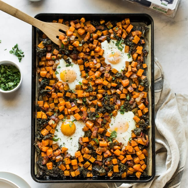 Sheet pan eggs and breakfast hash on a table next to plates.