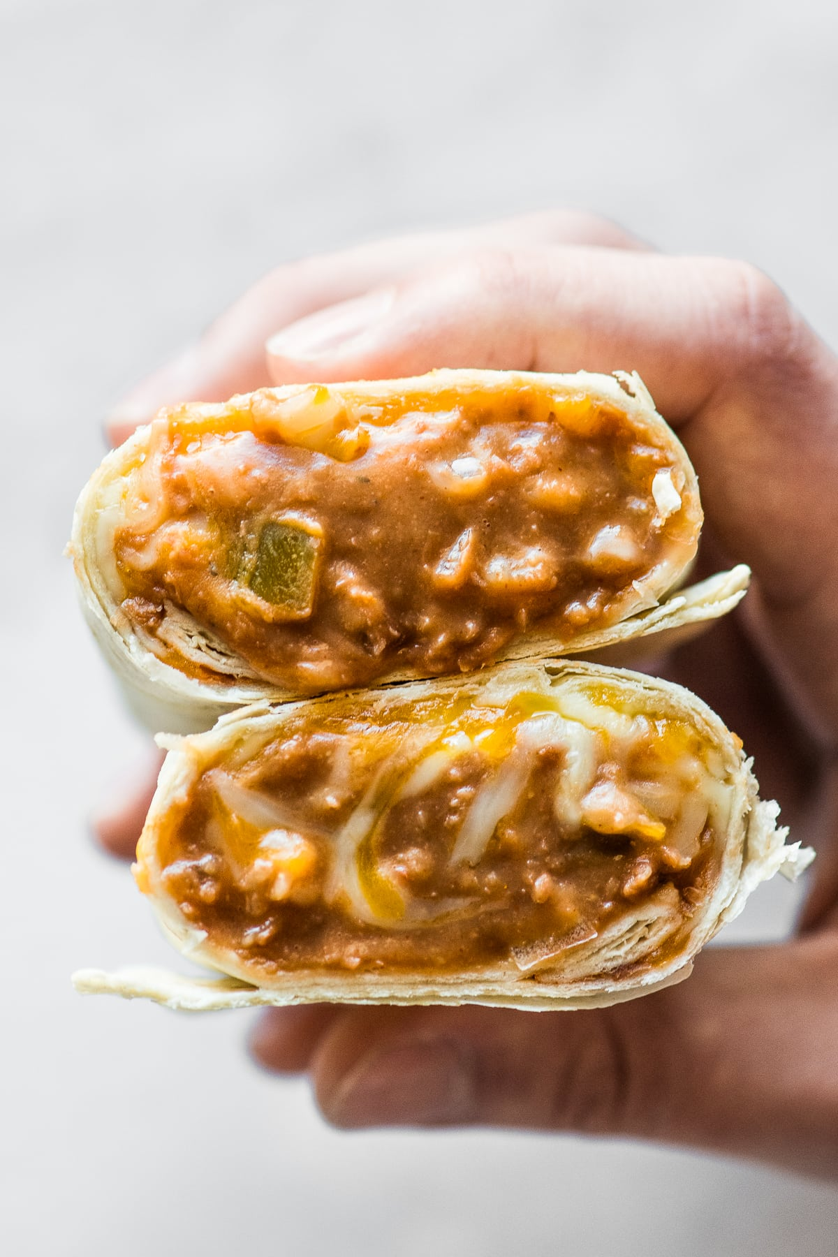 A bean and cheese burrito cut in half with the filling coming out.