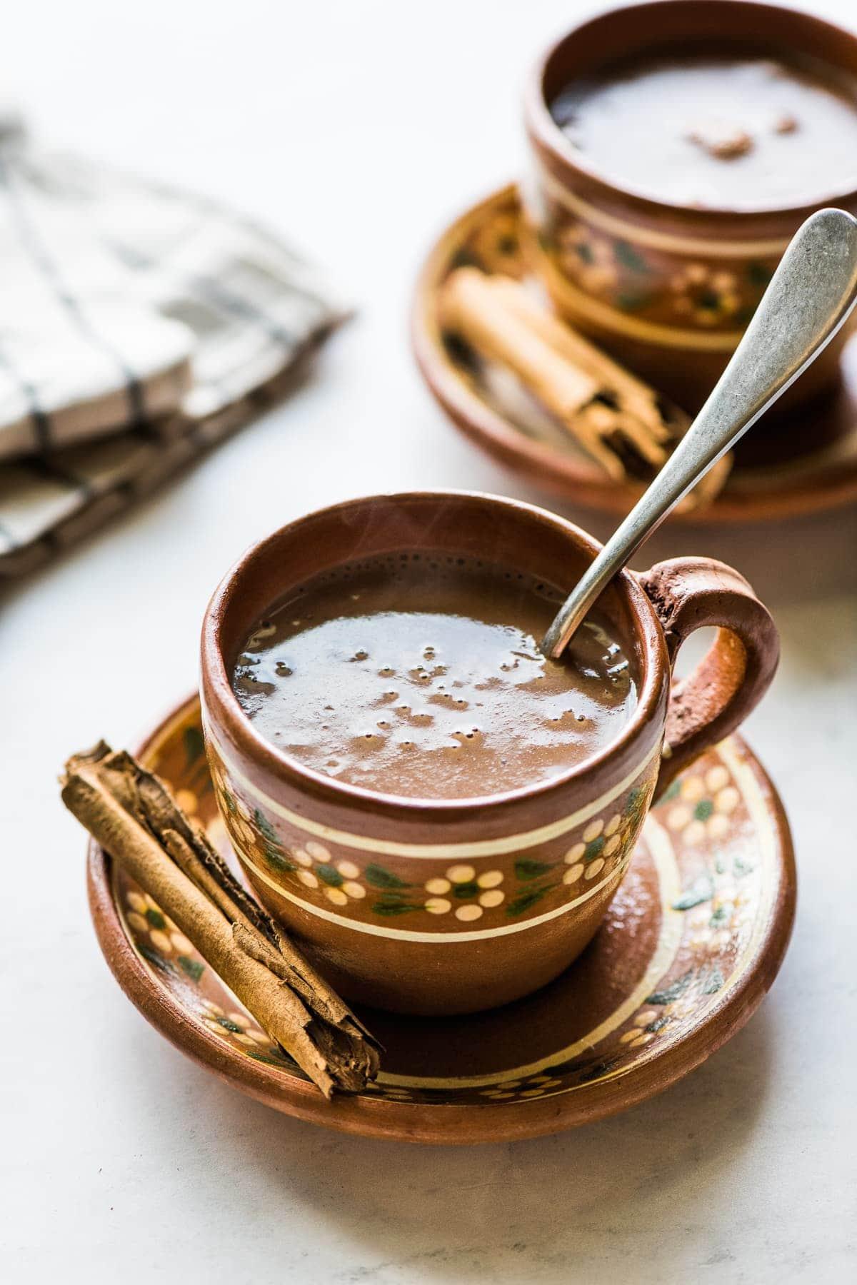 A mug of Mexican champurrado with a cinnamon stick.
