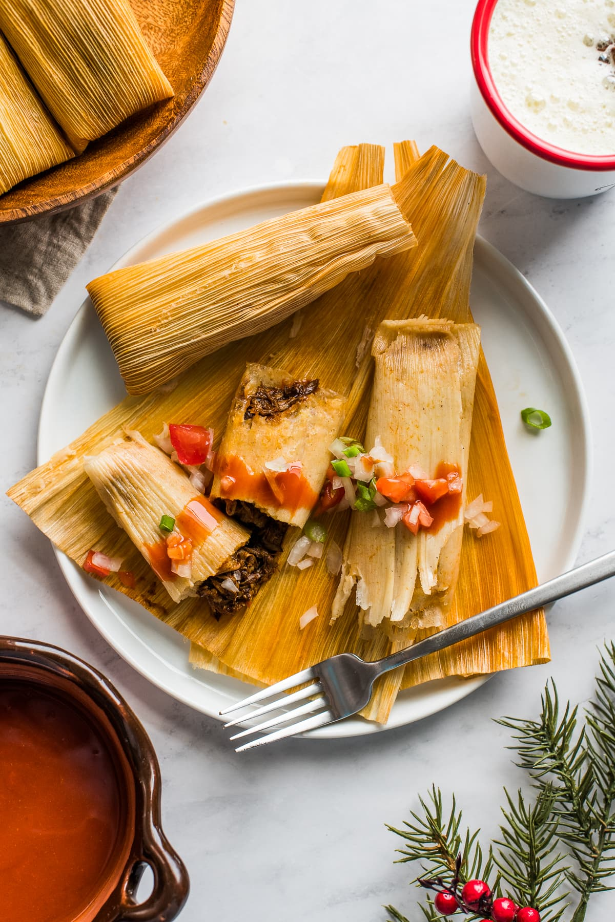 Instant Pot Tamales on a plate topped with tomatoes and onions.