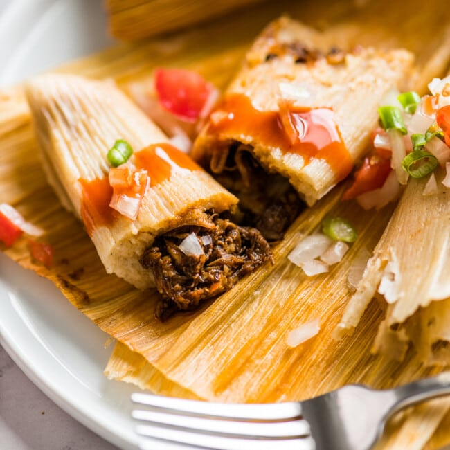An Instant Pot Pork Tamale cut in half to show the center.