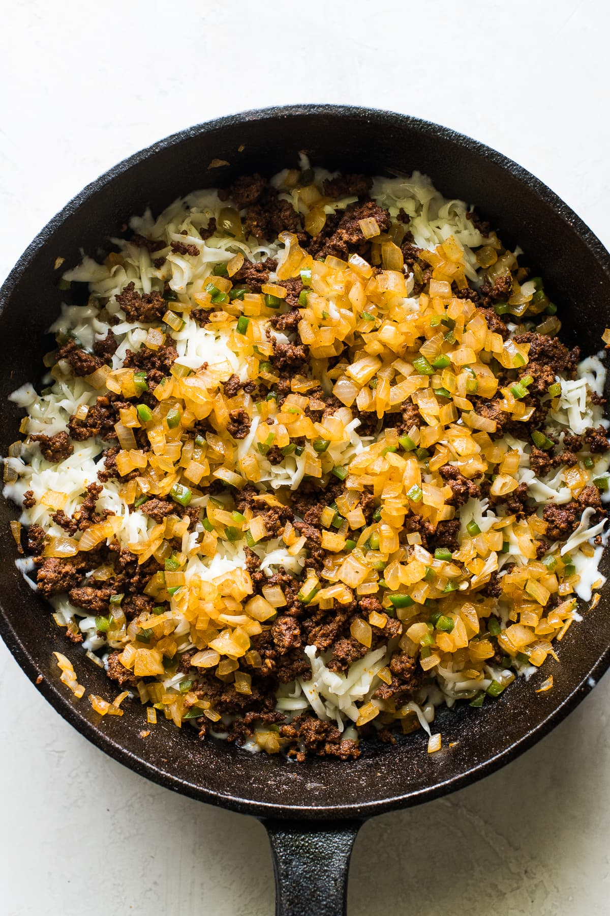 Sauteed onions, peppers, and chorizo in a skillet for queso fundido.