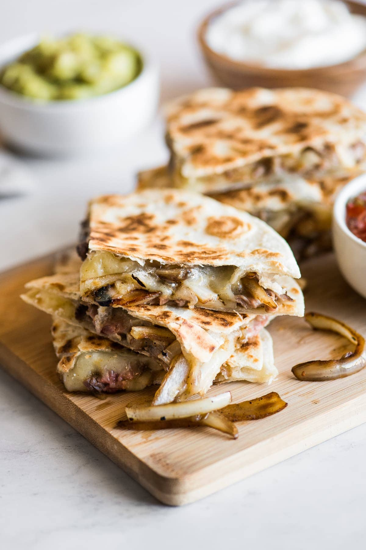Steak quesadillas with melted cheese and sauteed onions.