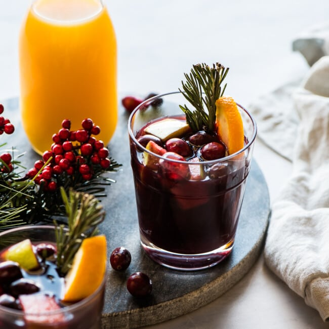 Winter sangria topped with cranberries, rosemary, and orange slices.
