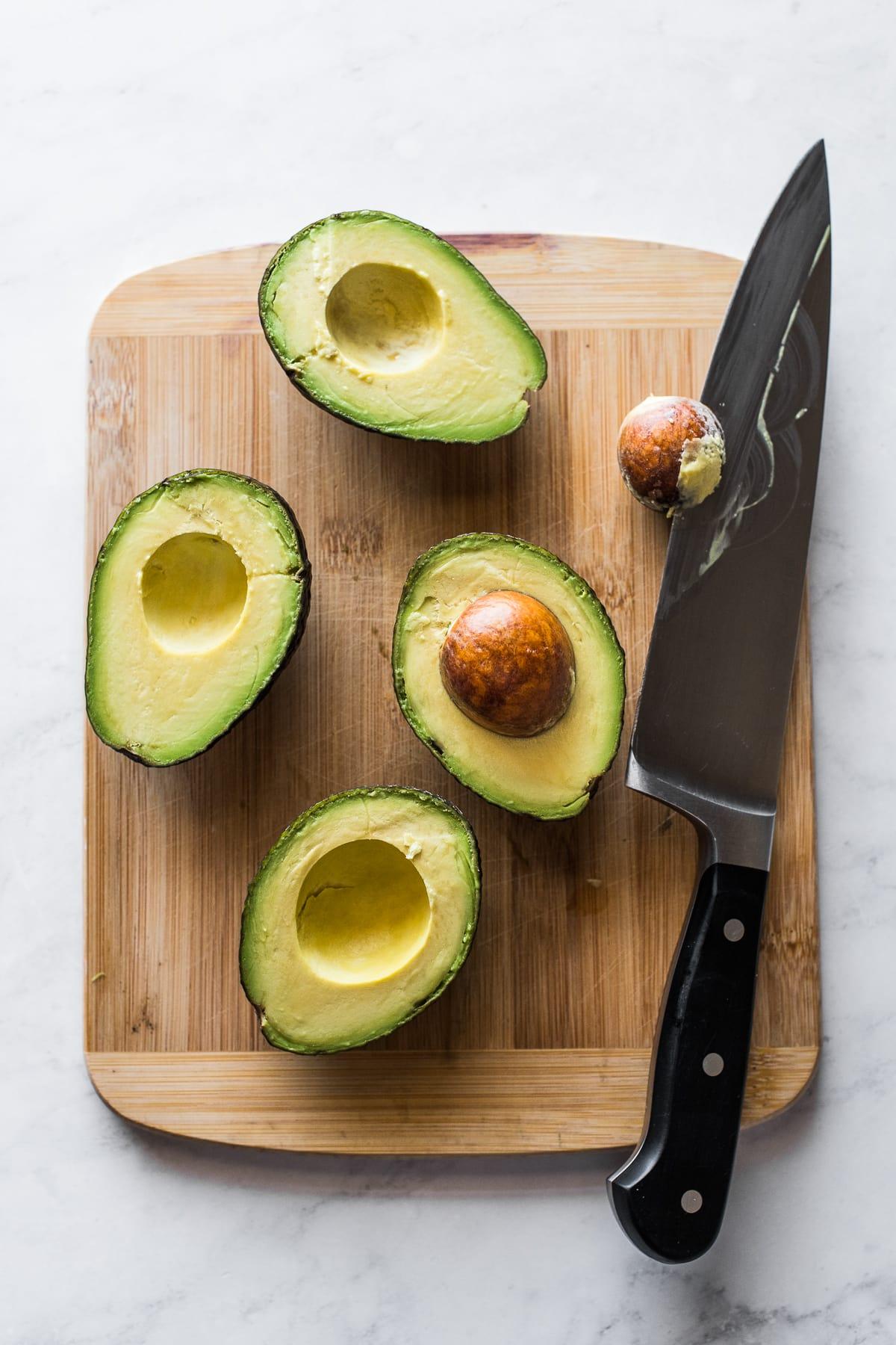 Avocado halves on a cutting board.