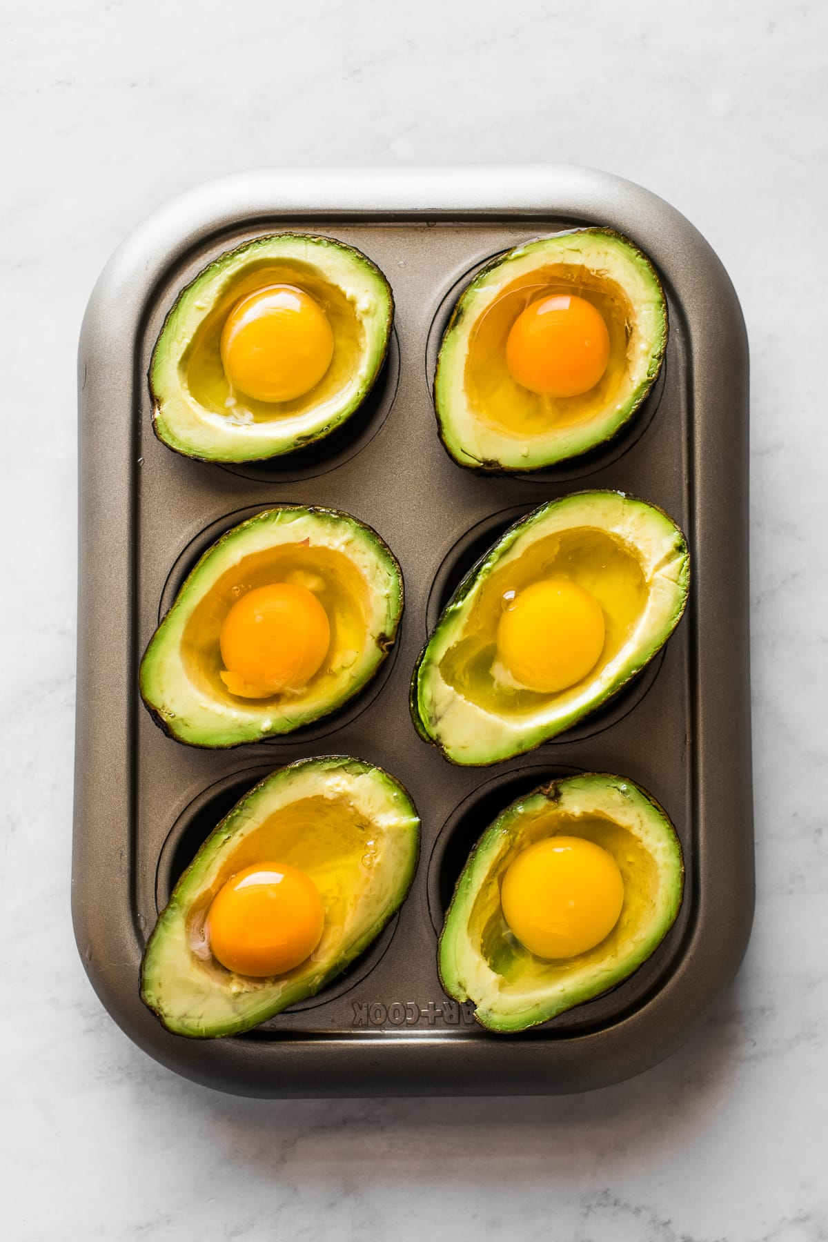 Avocado halves on a muffin tin with gently cracked eggs inside each well.