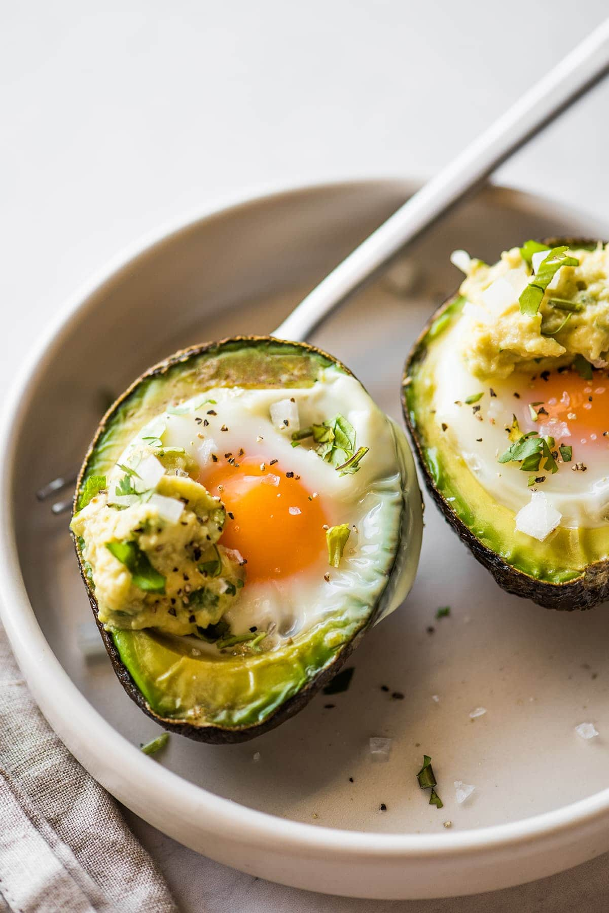 Avocado Egg Bake in a bowl seasoned with salt and pepper.