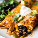 Black bean enchiladas topped with sour cream and cilantro.