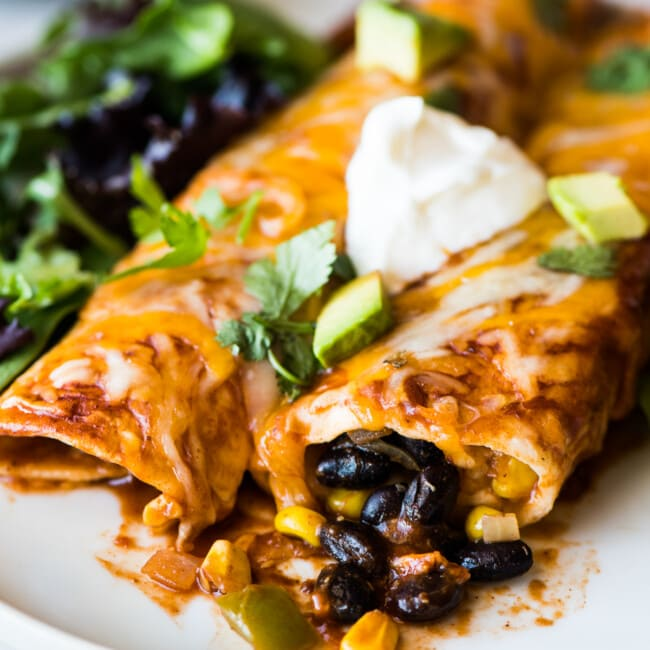 Black bean enchiladas topped with sour cream and cilantro.
