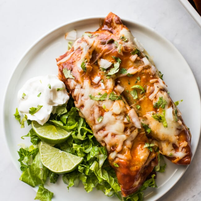 Turkey enchiladas on a plate with lettuce and sour cream.