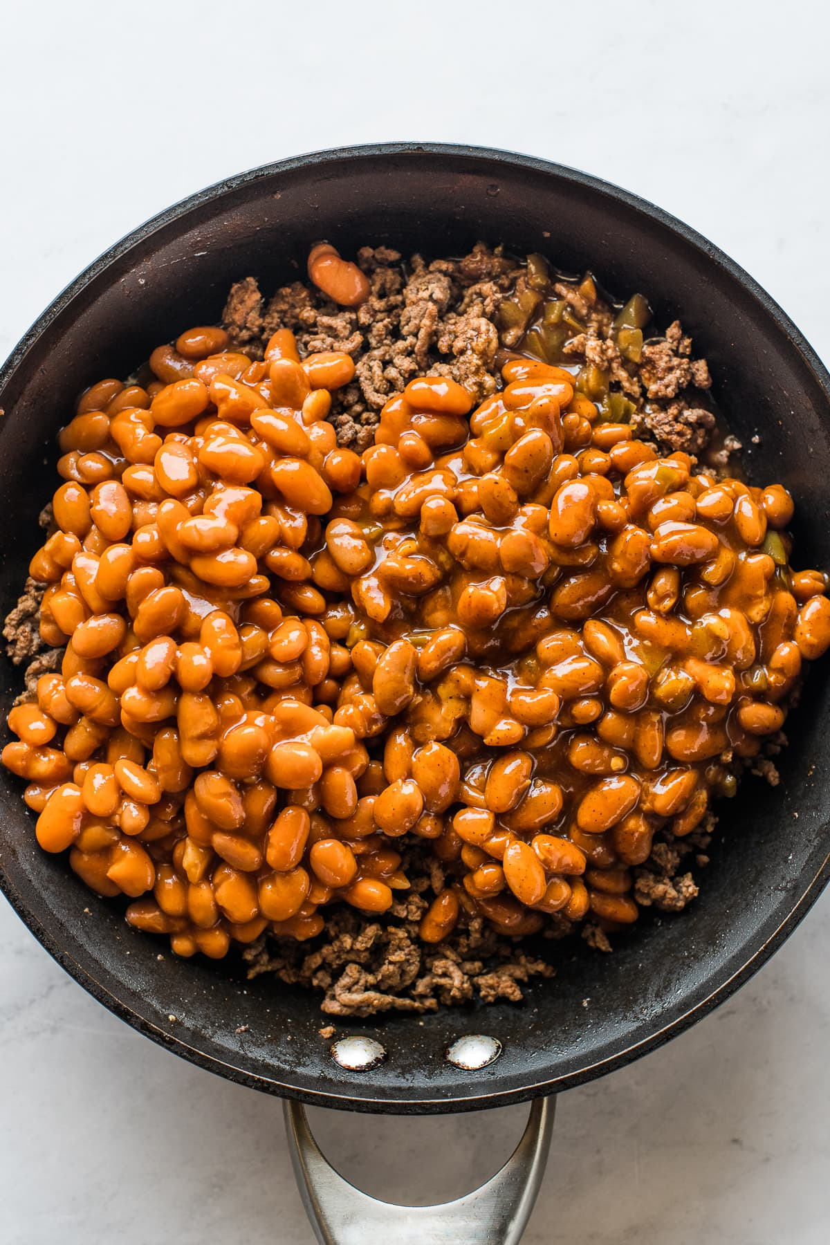 A skillet of beans and ground beef for walking tacos.