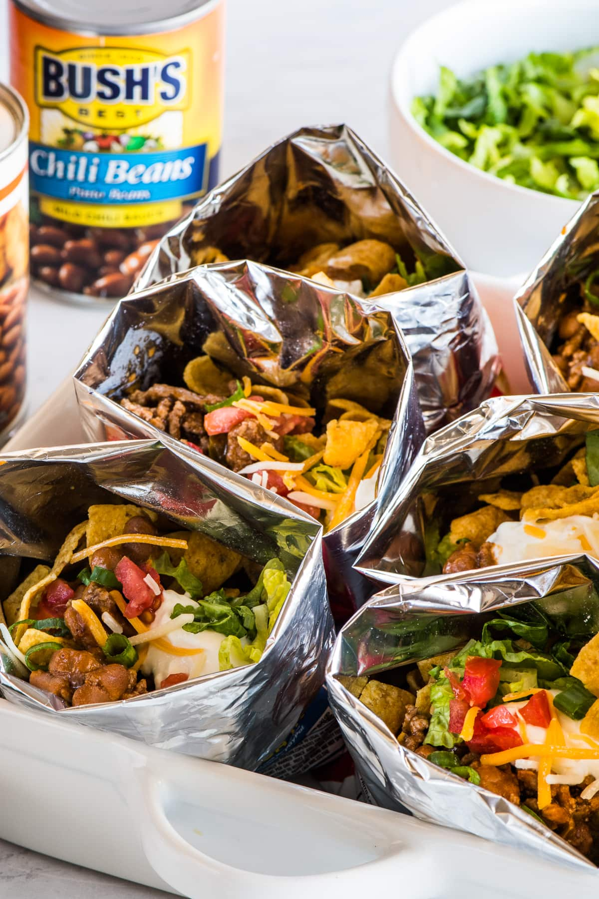 Bags of walking tacos on a table with all the toppings.