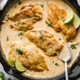 Pollo en Chipotle (Creamy Chipotle Chicken) in a skillet topped with cilantro and lime wedges.