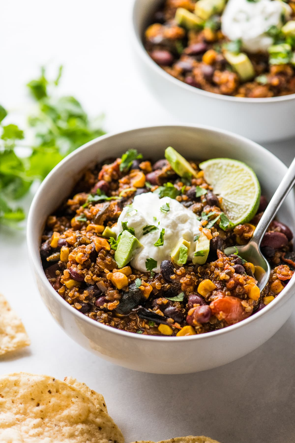 A bowl of vegetarian black bean and quinoa chili with a spoon.