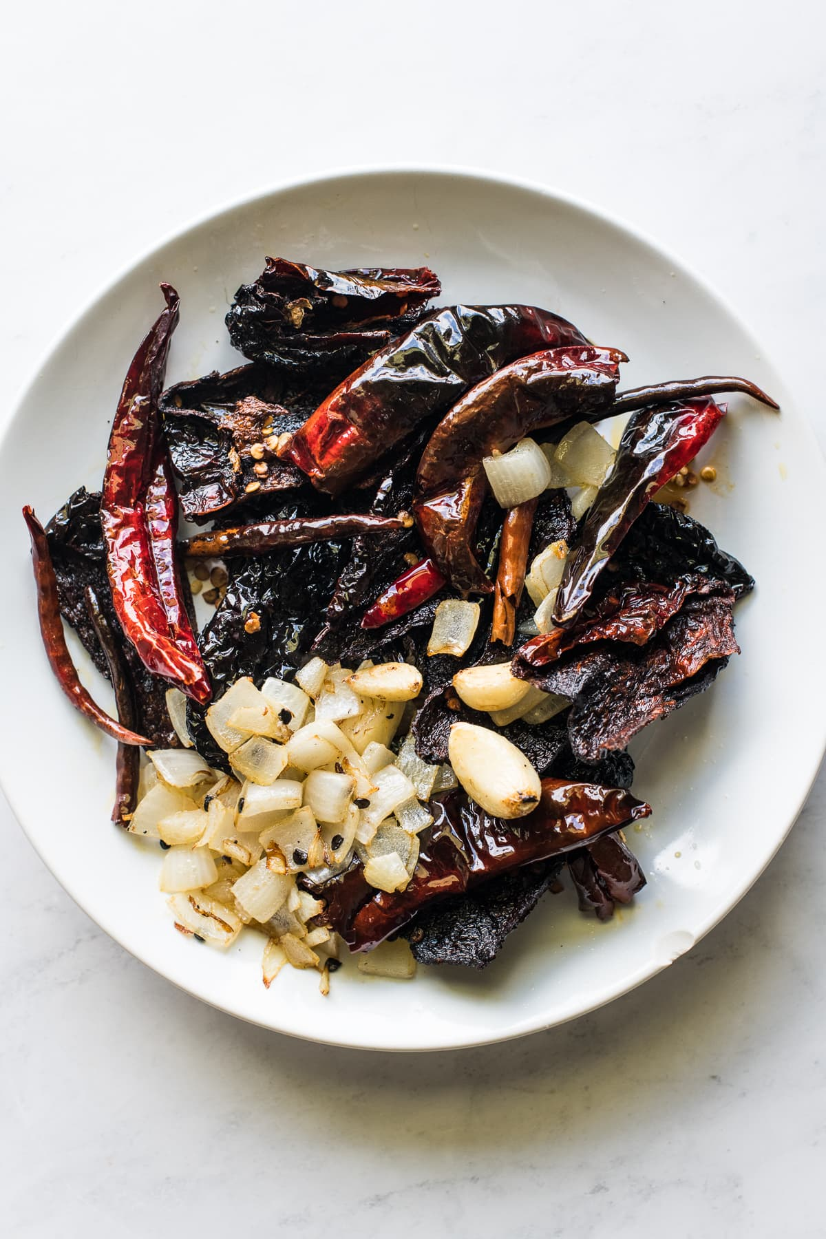 A plate full of sauteed chiles, onions, and garlic for salsa macha.
