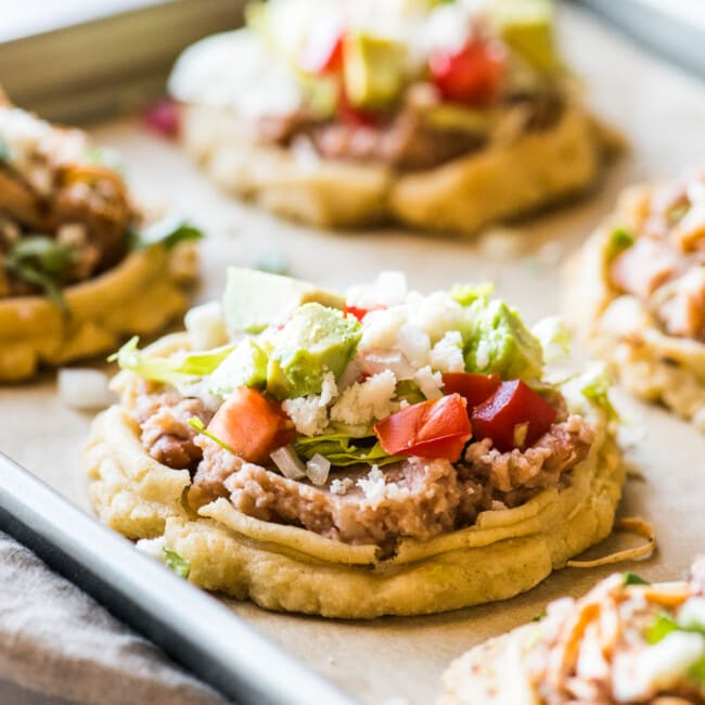 Sopes on a baking sheet topped with refried beans, lettuce, and tomatoes.