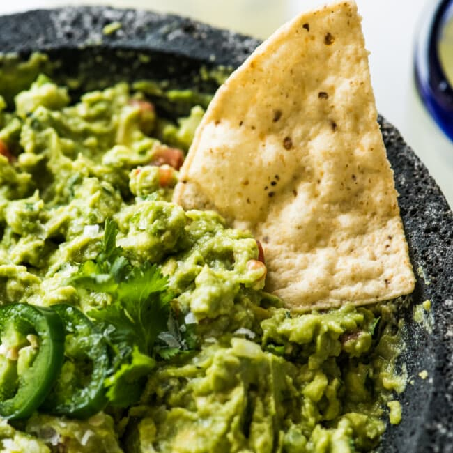 A tortilla chip being dipped in guacamole.