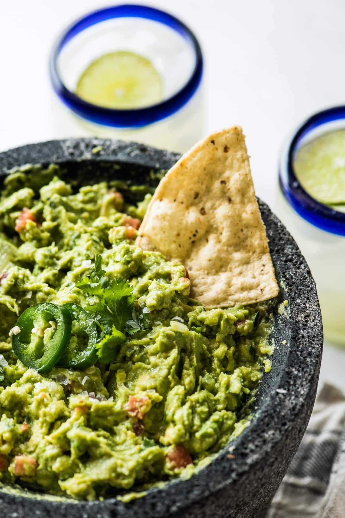 A simple guacamole recipe garnished with cilantro and jalapenos.