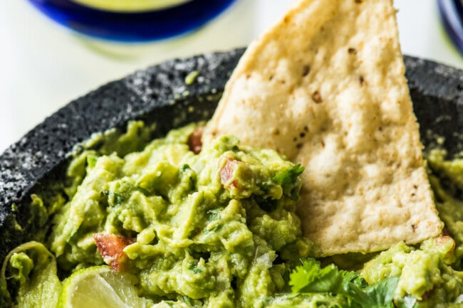 Guacamole in a molcajete with a tortilla chip.